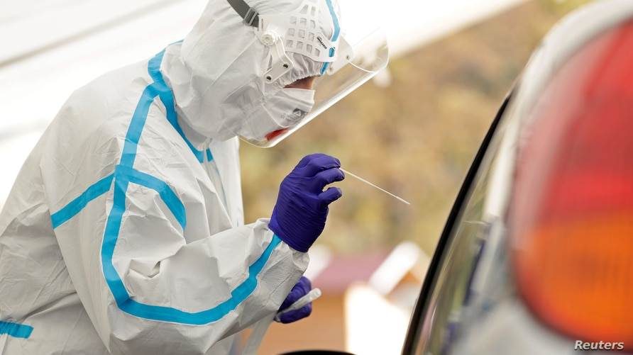 A medical staff member wearing a protective suit takes a swab sample of a person at a newly opened drive-in sampling station in Prague, Czech Republic, Oct. 7, 2020.