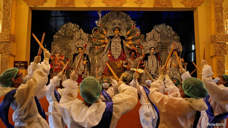 Hindu devotees wearing personal protective equipment perform Dandiya, a traditional dance, in front of an idol of Hindu goddess Durga on the first day of Durga Puja festival in Kolkata, India, Oct. 22, 2020.