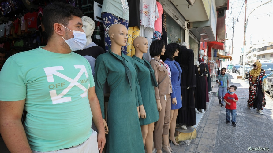 A vendor wearing a face mask stands in front of his school uniform shop in Amman, Jordan, Aug. 31, 2020.