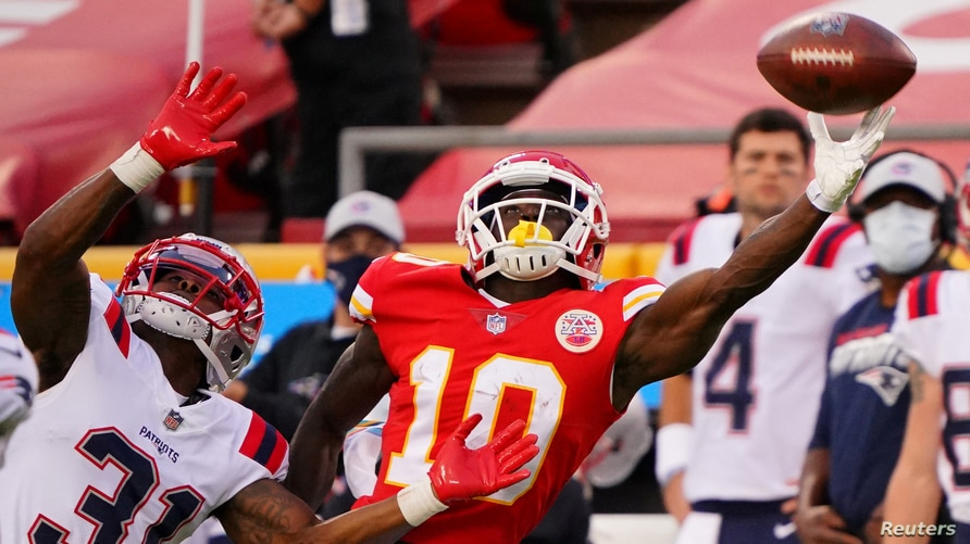 Kansas City Chiefs wide receiver Tyreek Hill (10) tries to catch a pass against New England Patriots defensive back Jonathan Jones (31) during the first quarter of a NFL game in Kansas City, Missouri, Oct. 5, 2020.