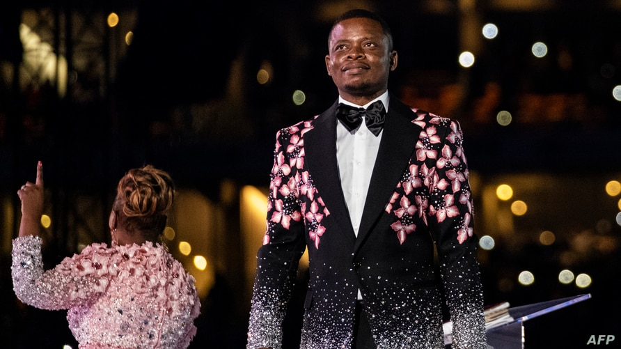 Pastor Shepherd Bushiri (R), also known as Prophet Bushiri from the Enlightened Christian Gathering (ECG), stands on stage…