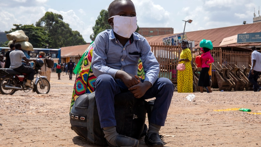 A boy sits on a bag at the old taxi park in Kampala, Uganda, on June 04, 2020, the first day of re-opening public transport. -…