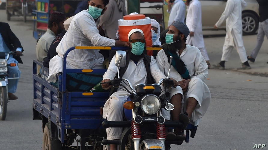 Pakistani Muslims wearing facemasks as a preventive measure against the Covid-19 coronavirus arrive for the annual Tablighi…