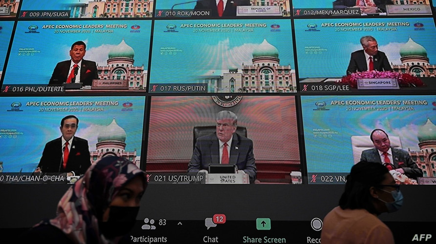 People walk in front of the virtual meeting monitor showing world leaders including US President Donald Trump (C) before the…