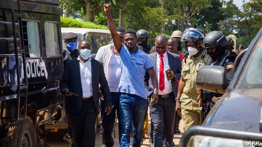 Ugandan musician turned politician Robert Kyagulanyi (C), also known as Bobi Wine, raises his arm as he walks to the court in…