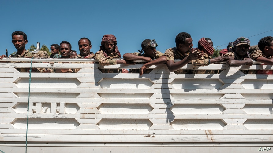 Members of the Amhara special forces look out from the back of a parked truck in Dansha, Ethiopia, on November 25, 2020. (Photo…