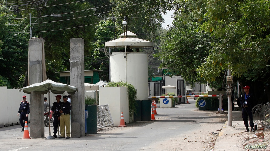 A policeman (2nd R) and private security personnel stand guard at the entrance of a road leading towards the U.S. consulate in…