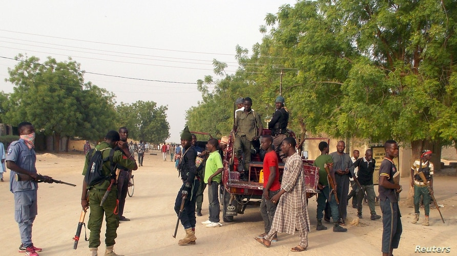 Local volunteers carrying weapons stand in the Jiddari Polo area in the northeastern city of Maiduguri, after an attack by Boko…