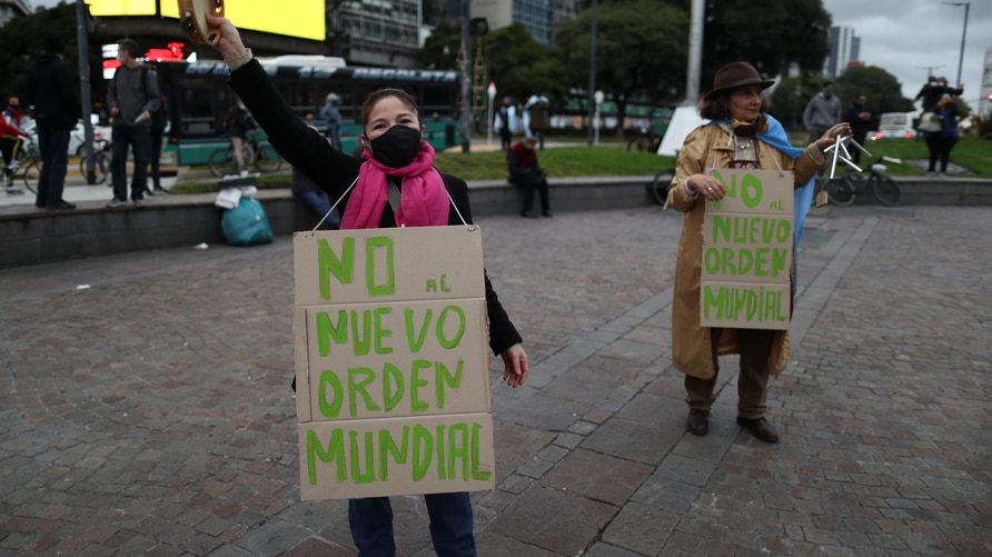 """Anti-quarantine demonstrators hang placards that reads """"no to the new world order"""""""