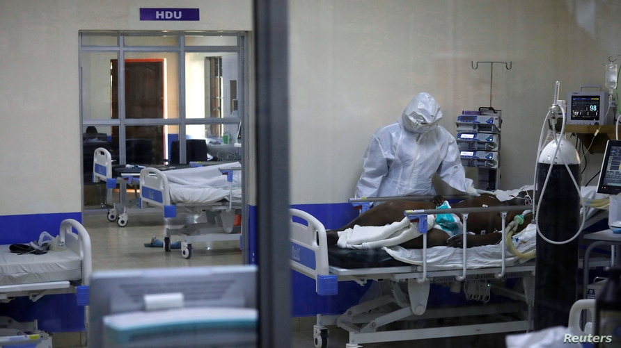 A member of the medical staff dressed in a protective suit treats a coronavirus disease patient inside the COVID-19 ICU of Machakos Level 5 Hospital, in Machakos, Kenya, Oct. 28, 2020. Picture taken Oct. 28, 2020.
