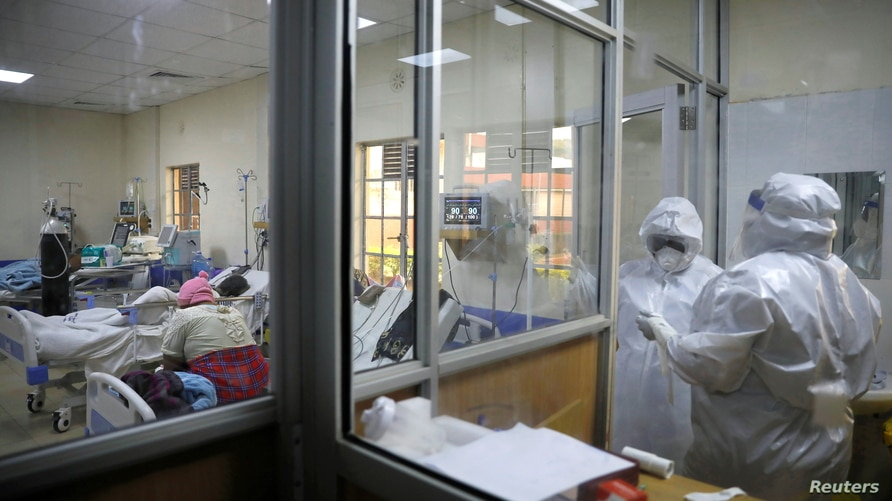 Medical staff dressed in protective suits talk to each other as they treat coronavirus disease patients at the COVID-19 ICU of…