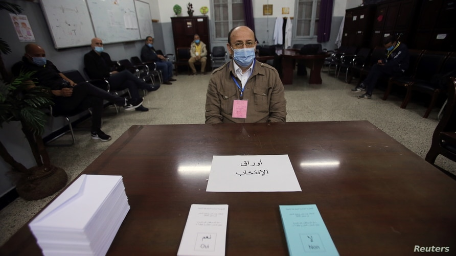 An electoral worker wearing a face mask for protection against the coronavirus disease (COVID-19), looks on at a polling station where Algerians vote in a constitutional referendum in Algiers, Algeria, Nov. 1, 2020.