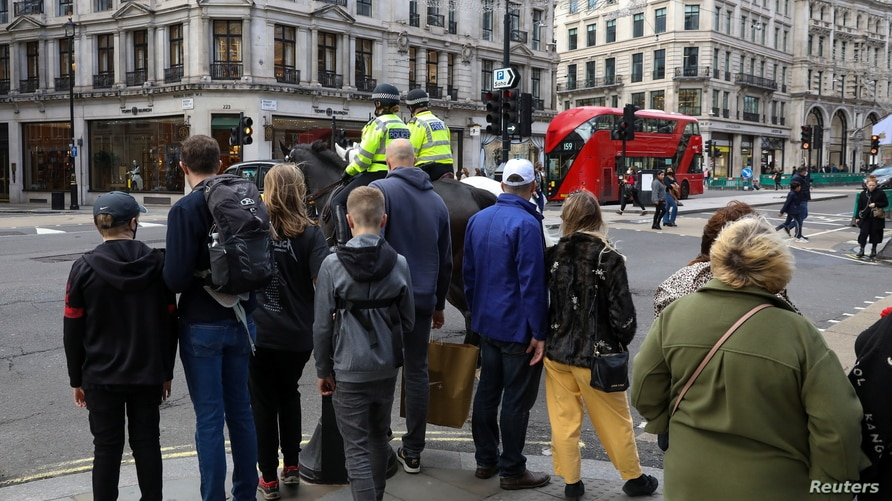 People wait to cross Regent Street, one of London's main shopping streets, a day after a new lockdown was announced during the…