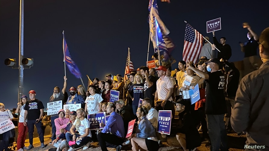 """Supporters of U.S. President Donald Trump, hold American flags and placards as they pose during a """"Stop the Steal"""" protest."""
