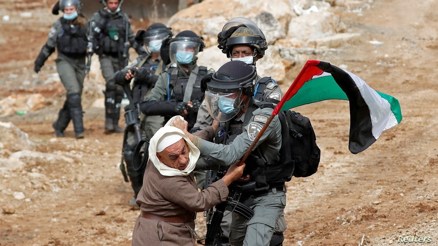 A Palestinian demonstrator scuffles with an Israeli border police member during a protest against Jewish settlements and U.S. President Donald Trump, in Beit Dajan in the Israeli-occupied West Bank, Nov. 6, 2020.