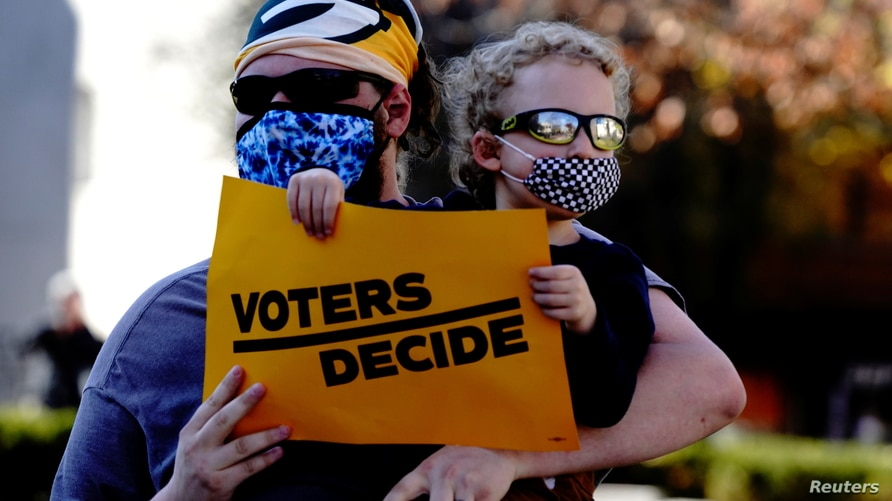 "A Biden supporter holds a sign reading ""voters decide"" at a 'Stop the Steal' protest in Madison, Wisconsin."
