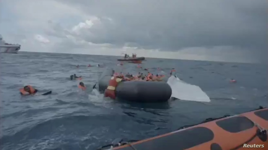 A still image taken from a video shows migrants at sea waiting to be rescued by Spanish search and rescue ship Open Arms during…