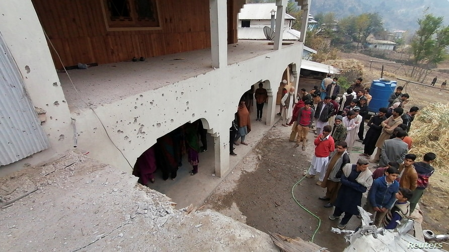 Locals gather near a house, which was damaged, according to them, by cross-border shelling, in Neelum Valley, in Pakistan…