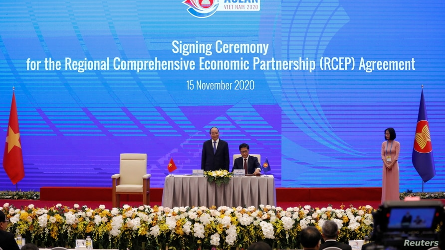 Vietnam's Industry and Trade Minister Tran Tuan Anh (C) signs as Vietnam's PM Nguyen Xuan Phuc (L) witnesses during the signing ceremony of the Regional Comprehensive Economic Partnership Agreement during the 37th ASEAN Summit in Hanoi, Nov. 15, 2020.