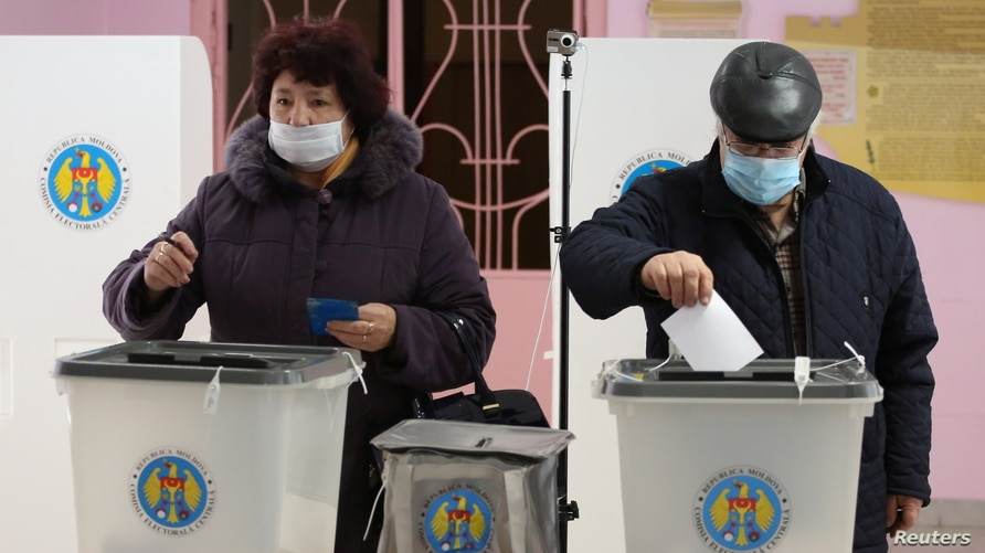 People cast their ballots at a polling station during the second round of a presidential election in Chisinau, Moldova November…