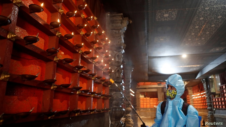 A man in personal protective equipment (PPE) sanitizes a temple before they reopen for the public amid the spread of the…