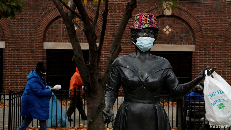 A bronze statue of late singer Ella Fitzgerald is seen wearing a hat and protective face mask, as the global outbreak of the…