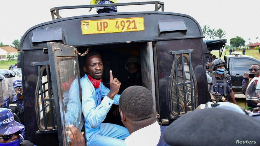 Ugandan presidential candidate Robert Kyagulanyi also known as Bobi Wine sits inside a police vehicle in Luuka district,…