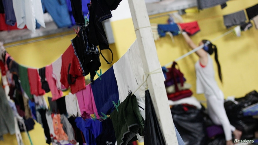 Clothes hang on a line to dry at a shelter for people affected by the floods caused by heavy rain brought by Storm Iota, in San…