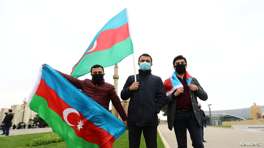 People pose with national flags as they celebrate the entry of the Azerbaijan army units in the Aghdam region.
