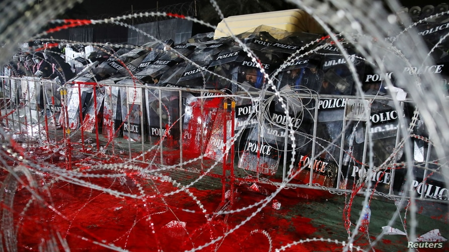 Riot police cover themselves with shields as they guard behind barb wires covered with red paint during a pro-democracy rally…