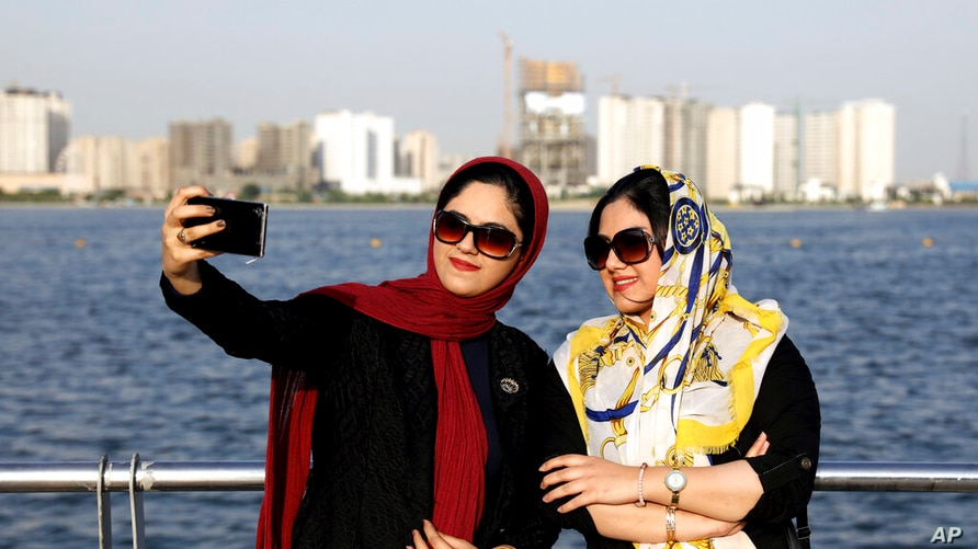 In this Saturday, July 7, 2019, photo, Iranians take selfie around of the Persian Gulf Martyrs lake, west of Tehran, Iran.  A…