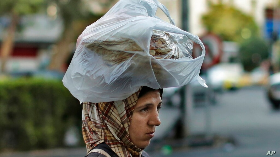 FILE - In this July 24, 2019 file photo, a woman carries bread on her head while she crosses a street in the Syrian capital,…