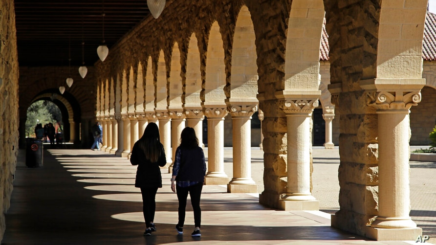 FILE- In this March 14, 2019, file photo students walk on the Stanford University campus in Santa Clara, Calif. Even with a…