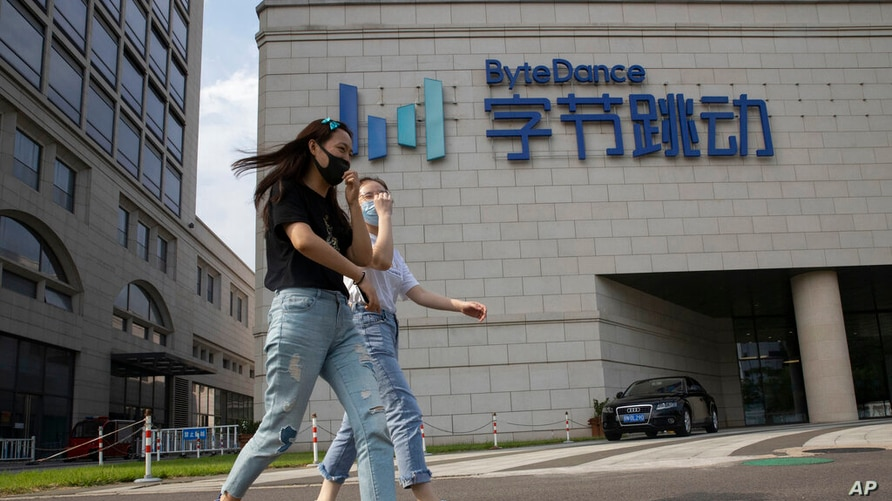 FILE - In this Aug. 7, 2020, file photo, women wearing masks to prevent the spread of the coronavirus chat as they pass by the headquarters of ByteDance, owners of TikTok, in Beijing, China.