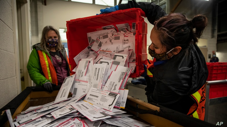 Election worker Kristen Mun from Portland empties ballots from a ballot box at the Multnomah County Elections Division.