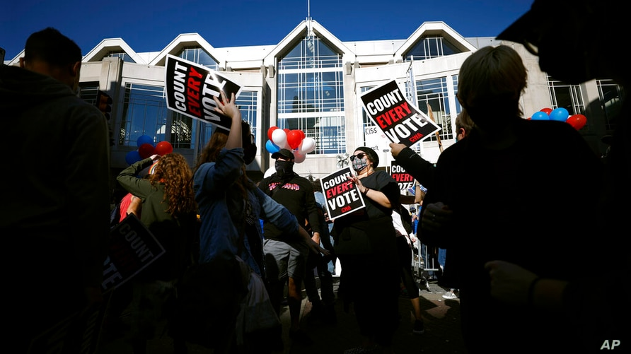 People demonstrate outside the Pennsylvania Convention Center where votes are being counted, Friday, Nov. 6, 2020, in…