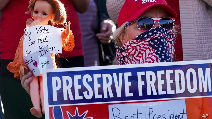 FILE- In a Nov. 7, 2020 file photo, a supporter of President Donald Trump is seen during a rally in Milwaukee after it was…