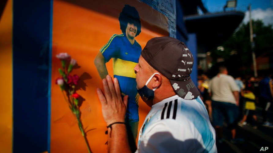 A soccer fan kisses a poster of Diego Maradona at the entrance of the Boca Juniors stadium, known as La Bombomera, in Buenos…