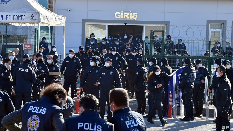 Riot police officers stand at the entrance of a courthouse during the trial of 475 defendants, including generals and fighter…