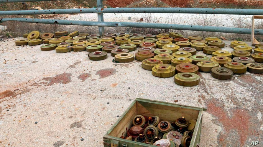 In this photo released by the Syrian official news agency SANA, landmines are collected by Syrian engineering troops from the M5 highway, recaptured by President Bashar Assad's forces this week, in Aleppo, Syria, Feb. 15, 2020.