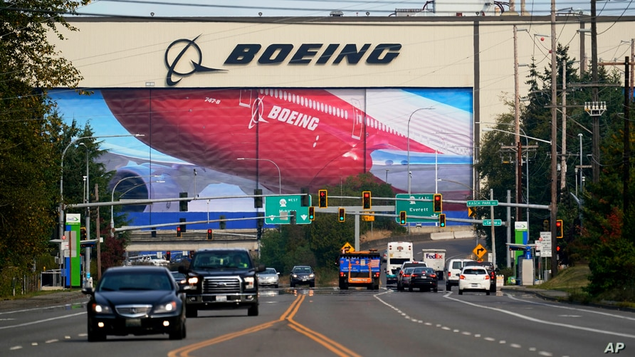 FILE - Traffic passes in view of a massive Boeing airplane production plant, Oct. 1, 2020, in Everett, Wash. Boeing failed to…