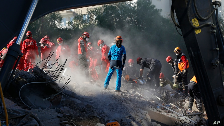 Members of rescue services search for survivors in the debris of a collapsed building in Izmir, Turkey, Nov. 2, 2020.