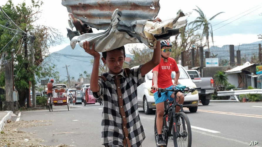A boy carries metal sheets that were blown away from houses in the winds of Typhoon Goni in Albay province, central Philippines…