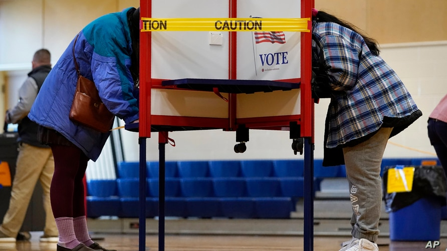Caution tape closes off a voting stall to help distance voters to help prevent the spread of the coronavirus during Election…