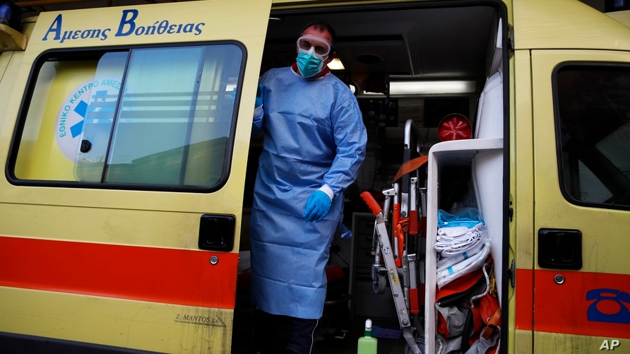 A paramedic wearing a suit to protect against coronavirus, closes the door of an ambulance at Evangelismos hospital in Athens, Nov. 12, 2020.