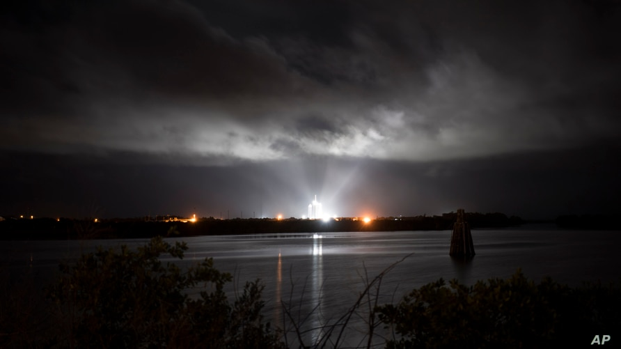 A SpaceX Falcon 9 rocket with the company's Crew Dragon spacecraft onboard is seen illuminated by spotlights on the launch pad at Launch Complex 39A, Saturday, Nov. 14, 2020, at NASA's Kennedy Space Center, at Cape Canaveral, Fla.