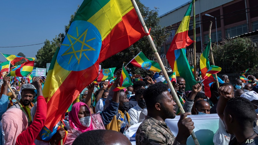 Ethiopians hold national flags as they gather at an event organized by city officials to honor the Ethiopian military, at the…