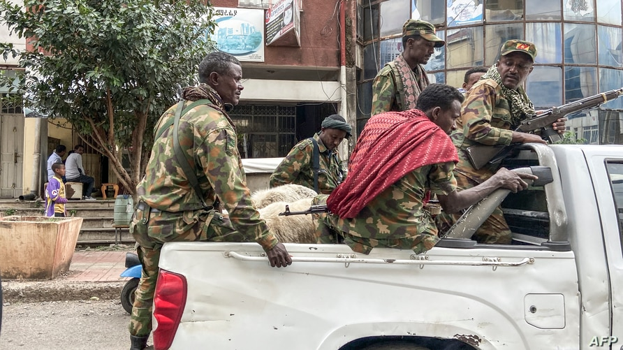 Members of the Amhara militia that sides with federal and regional forces against the northern region of Tigray ride on the back of a pick up truck in the city of Gondar, Ethiopia, Nov. 8, 2020.