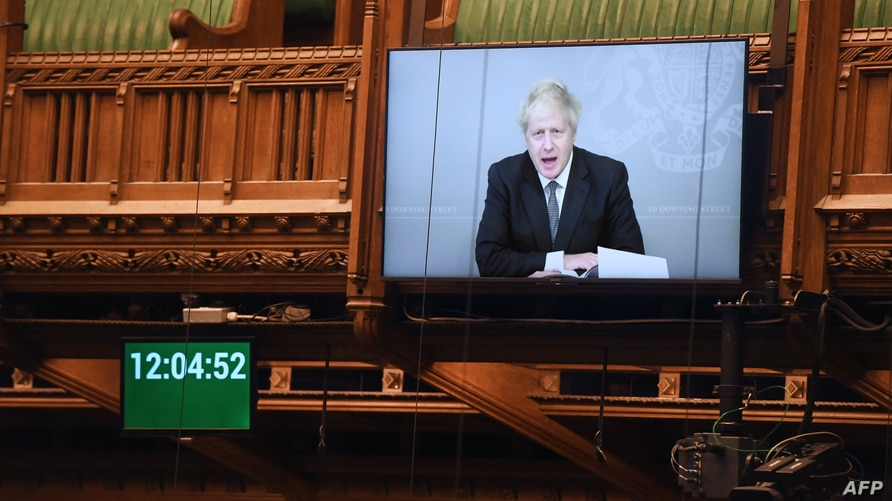 A handout photograph released by the UK Parliament shows a screen displaying an image of Britain's Prime Minister Boris Johnson as he takes questions remotely during a socially distanced session in the House of Commons, in London, Nov. 18, 2020.