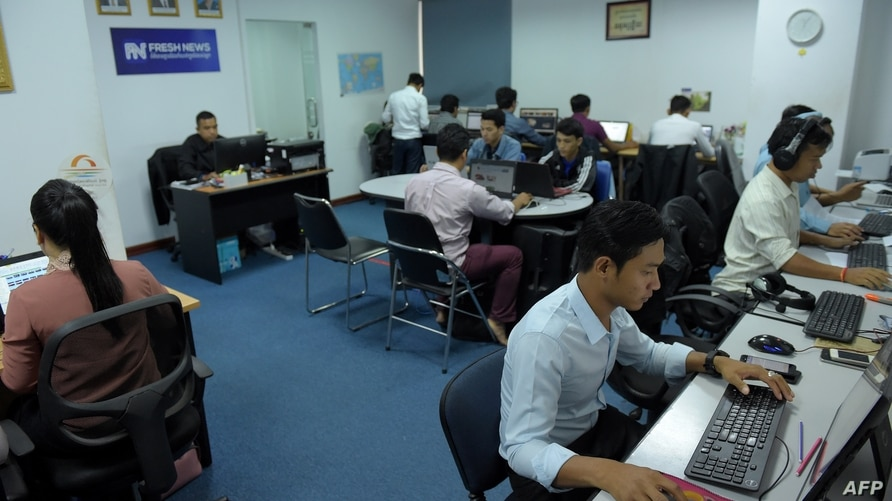 FILE - Cambodian online news outlet 'Fresh News' staff members work in their newsroom in Phnom Penh, May 21, 2018.